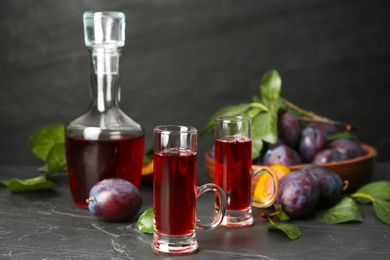Delicious plum liquor and ripe fruits on black table. Homemade strong alcoholic beverage