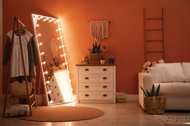 Large mirror with light bulbs and chest of drawers in stylish room interior