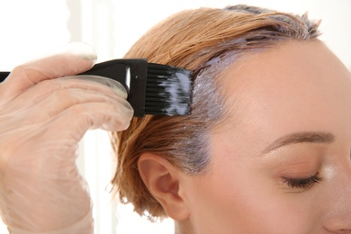 Young woman applying hair dye on roots against light background, closeup