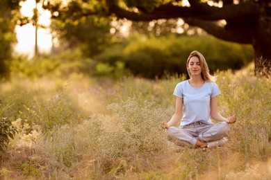 Young woman meditating on green grass in park, space for text