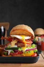 Serving pan with juicy bacon burger on wooden board