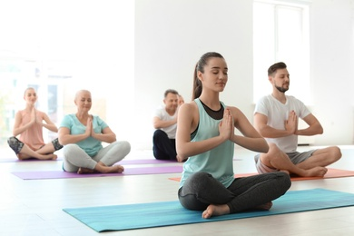 Group of people in sportswear practicing yoga indoors