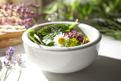 Bowl with healing herbs on white wooden table