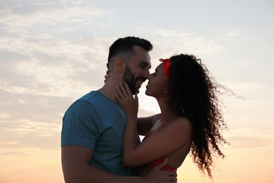 Lovely couple spending time together outdoors at sunset