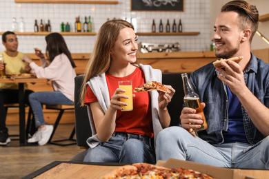 Young couple eating delicious pizza in cafe