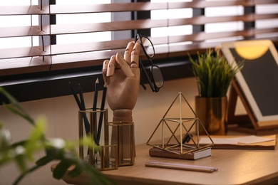 Stylish workplace with different accessories on table at window. Ideas for interior design