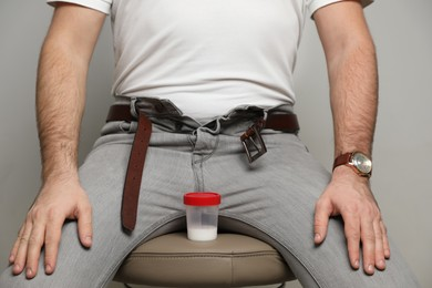 Donor with unzipped pants and container of sperm sitting on stool against beige background, closeup