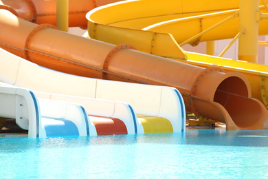 Different colorful slides in water park on sunny day