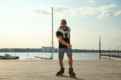 Handsome young man roller skating on pier near river