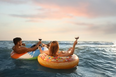 Couple with glasses of wine and inflatable rings in sea