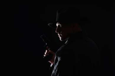 Old fashioned detective with gun on dark background. Space for text