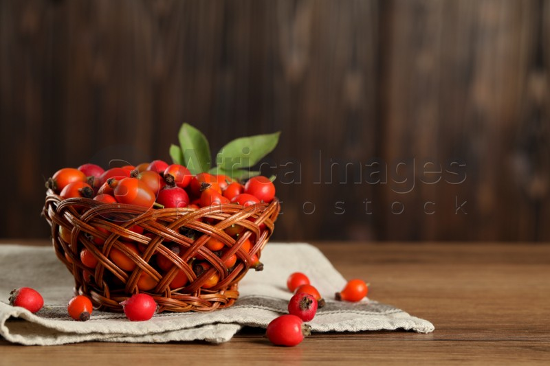 Ripe rose hip berries with green leaves on wooden table. Space for text