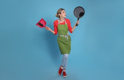 Young housewife with dustpan, brush, frying pan and spatula on light blue background