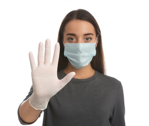 Woman in protective face mask and medical gloves showing stop gesture against white background, focus on hand