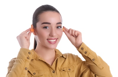 Young woman inserting foam ear plugs on white background