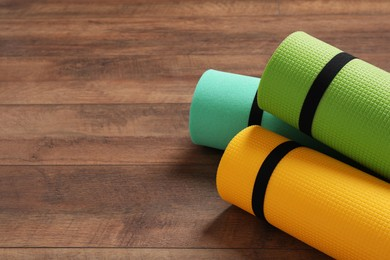 Bright rolled camping mats on wooden background. Space for text