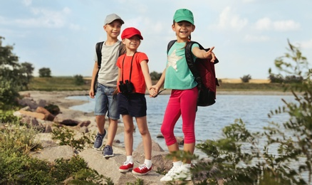 Cute little children with backpacks and binoculars on rock near river. Camping trip