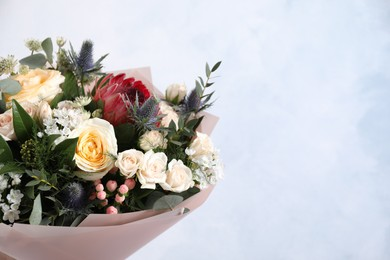 Beautiful bouquet with roses on light blue background. Space for text
