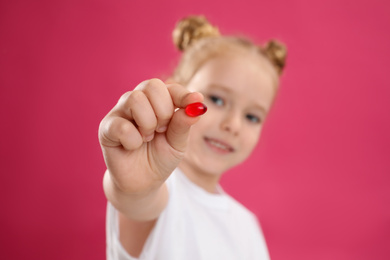 Little girl with vitamin pill against pink background, focus on hand