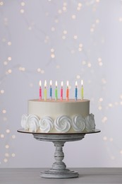 Birthday cake with burning candles on white table against blurred festive lights