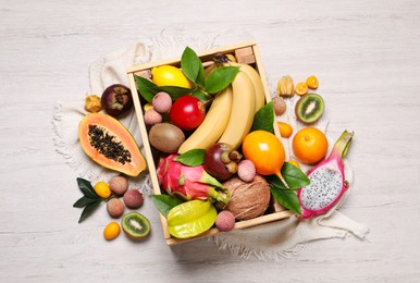 Crate and different exotic fruits on white wooden table, flat lay