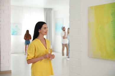 Young woman with glass of champagne at exhibition in art gallery
