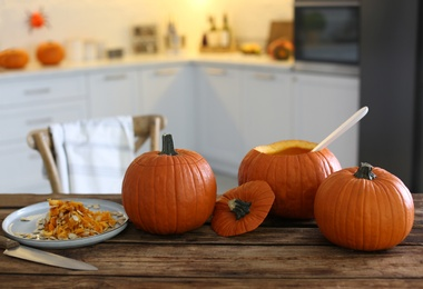 Fresh ripe pumpkins on wooden table in kitchen, space for text. Halloween celebration