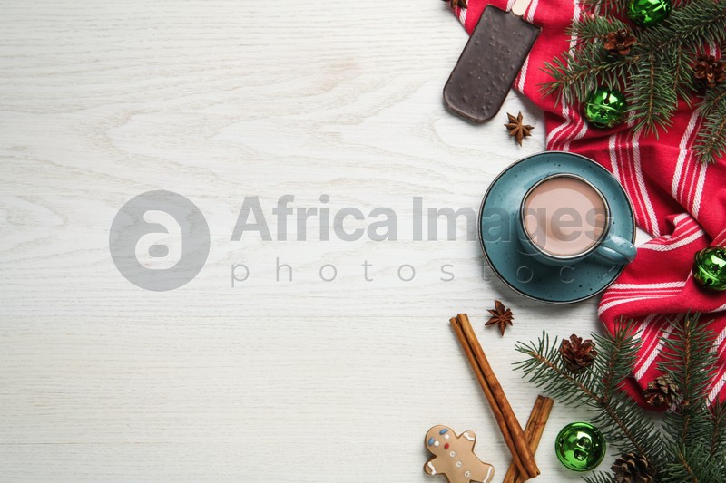 Delicious hot chocolate and Christmas decor on white wooden table, flat lay. Space for text