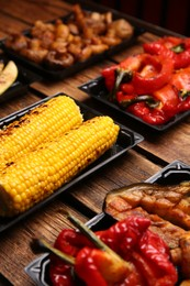 Plastic containers with different grilled meal on wooden table, closeup. Food delivery service