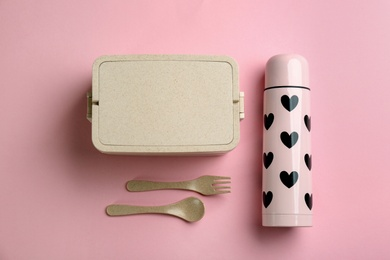 Thermos and lunch box with cutlery on pink background, flat lay