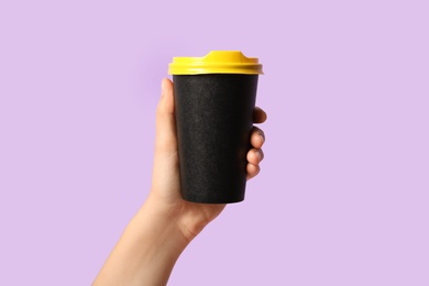Woman holding takeaway paper coffee cup on violet background, closeup