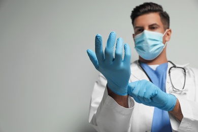 Doctor in protective mask and medical gloves against light grey background, focus on hands. Space for text