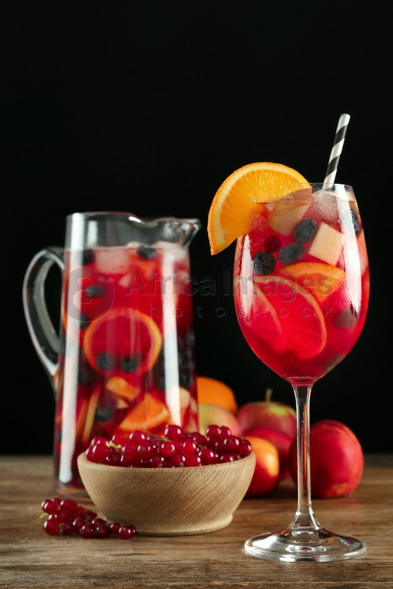 Glass and jug of Red Sangria with fruits on wooden table against black background