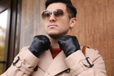 Handsome stylish man wearing black leather gloves outdoors, focus on hands