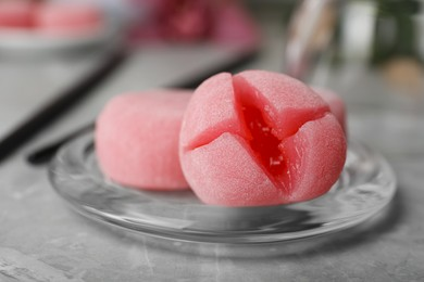 Glass plate with delicious mochi on grey table, closeup. Traditional Japanese dessert