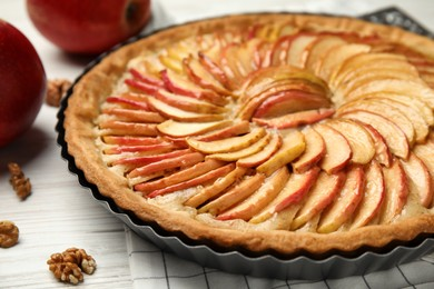 Delicious homemade apple tart on white wooden table, closeup
