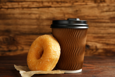 Delicious donut and cup of coffee on wooden table