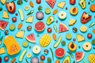 Flat lay composition with fresh organic fruits and vegetables on light blue background
