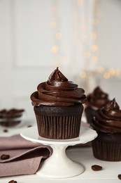 Dessert stand with delicious chocolate cupcake on white table against blurred lights. Space for text
