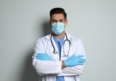 Doctor in protective mask and medical gloves against light grey background