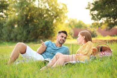 Happy young couple having picnic on green grass in park