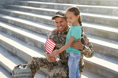Soldier and his little daughter with flag of USA outdoors, space for text