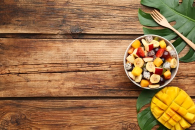 Delicious exotic fruit salad on wooden table, flat lay. Space for text