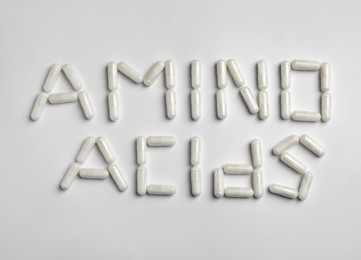 Phrase Amino acids made of pills on white background, flat lay