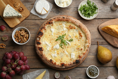 Delicious cheese pizza and fresh ingredients on wooden table, flat lay