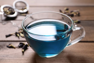 Glass cup of organic blue Anchan on wooden table, closeup. Herbal tea