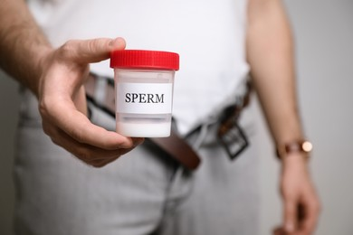 Donor with unzipped pants holding container of sperm, closeup