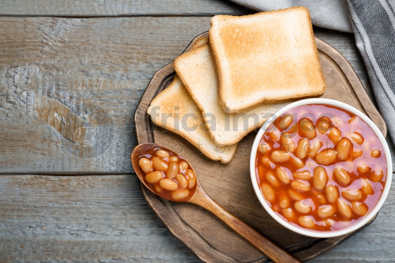 Toasts and delicious canned beans on wooden table, top view. Space for text