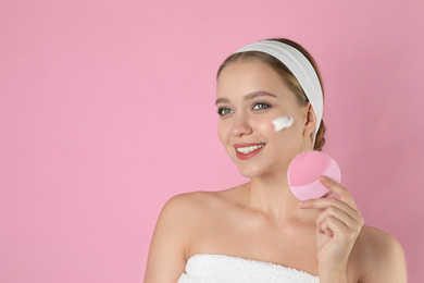Young woman washing face with brush and cleansing foam on pink background, space for text. Cosmetic product