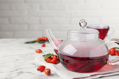 Fresh rose hip tea and berries on white marble table. Space for text